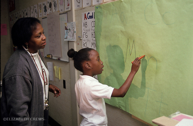 Oakland CA Teacher in learning handicapped class teaching student how to identify letters, using a projector