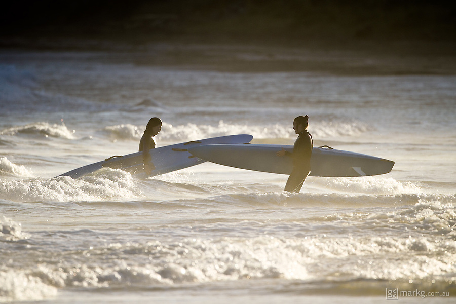 Two female board paddlers in the shallows after a late afternoon training session at Lyall Bay