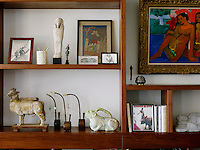 An eclectic mix of artwork and objects is displayed on the vesi wood wall unit in the library