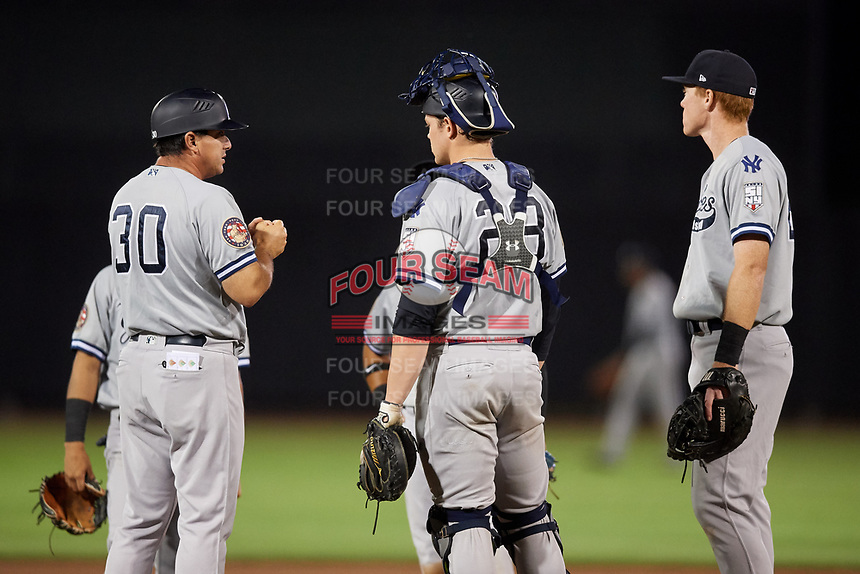 Staten Island Yankees manager Lino Diaz (30) waits on the mound with catcher Josh Breaux (28) and first baseman Eric Wagaman (22) after calling for a pitching change during a game against the Aberdeen IronBirds on August 23, 2018 at Leidos Field at Ripken Stadium in Aberdeen, Maryland.  Aberdeen defeated Staten Island 6-2.  (Mike Janes/Four Seam Images)