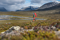 Single hiker hiking through Tjäktjavagge valley south of Sälka hut, Kungsleden trail, Lapland, Sweden