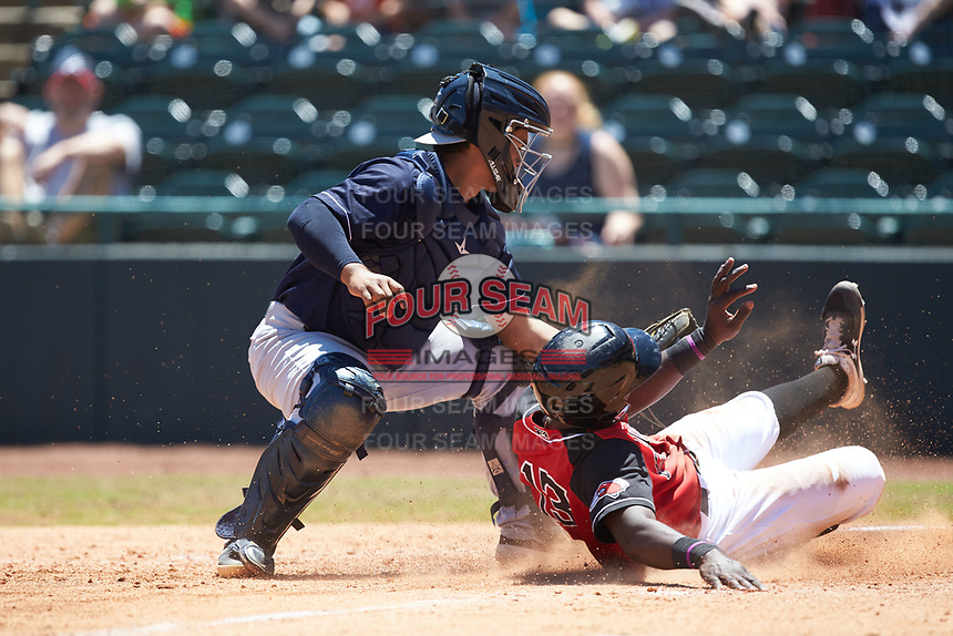 Charleston RiverDogs catcher Eduardo Navas (20) applies the tag to Sherten Apostel (13) of the Hickory Crawdads as he slides across home plate at L.P. Frans Stadium on May 13, 2019 in Hickory, North Carolina. The Crawdads defeated the RiverDogs 7-5. (Brian Westerholt/Four Seam Images)