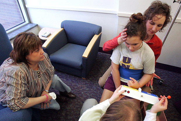 Elizabeth uses a two-button console to answer yes or no questions during a physical therapy session at Blank Children's Hospital, while her mother, Barb, looks on at left.  She answers yes after being asked if she wanted the sucker at bottom right.