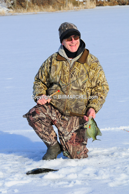 00247-012.14 Black Crappie: Angler had one fish on ice as he lands another.  Fish, lake, winter, river, angle.