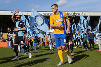 Paul Hayes of Wycombe Wanderers and Lee Collins of Mansfield Town enter the pitch ahead of the Sky Bet League 2 match between Wycombe Wanderers and Mansfield Town at Adams Park, High Wycombe, England on 25 March 2016. Photo by David Horn.