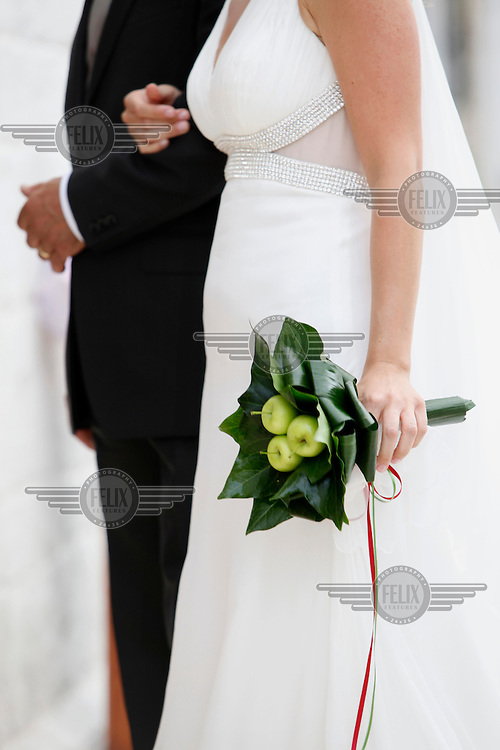 A bride walks arm-in-arm with her father.