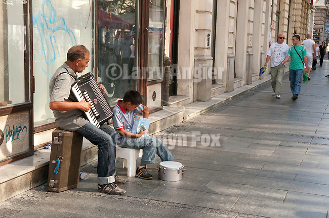 A man and boy play music on a street in Belgrade, Serbia.