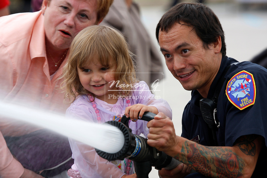 A young girl using a water hoseline to put out a fire at an educational display for National Night Out in Brown Deer Wisconsin