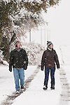 A couple walks along a snow-covered road during winter in the Sierra Nevada Foothills of central Calif. (Matt & Jamie)