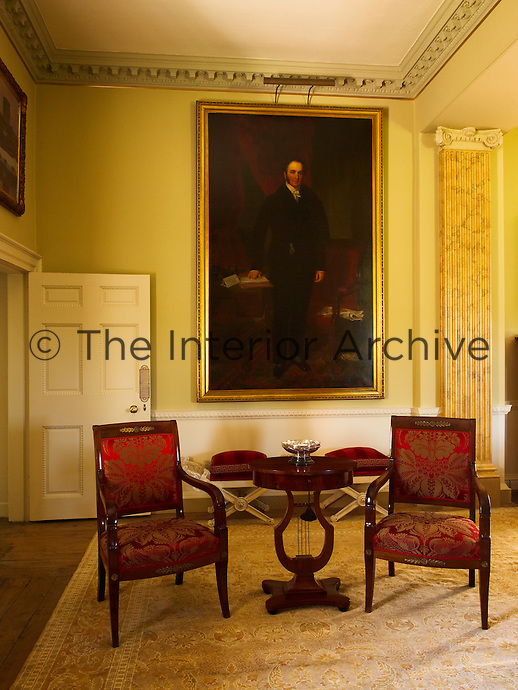 A pair of French Empire chairs stands next to a Swedish lyre table in front of 19th century portrait painting in the drawing room