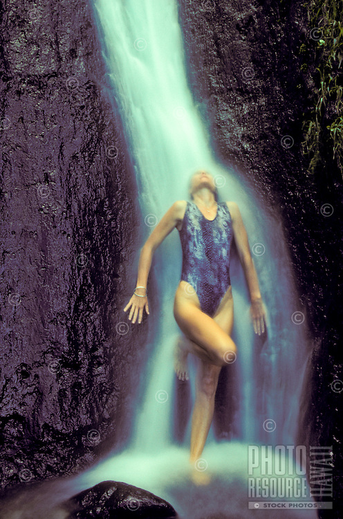 Woman standing under a waterfall on the Big island of Hawaii