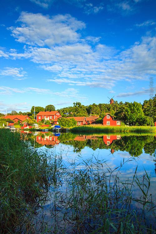 Faluröda hus och kvarnen på Utö speglas i vattnet i Stockholms skärgård