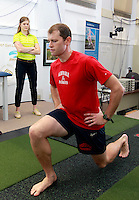 Biomechanical analyst Leigh Allin looks at the form and balance of Matt Clay as he performs simple stretches during a visit to the clinic in Charlottesville, VA. Photo/Andrew Shurtleff