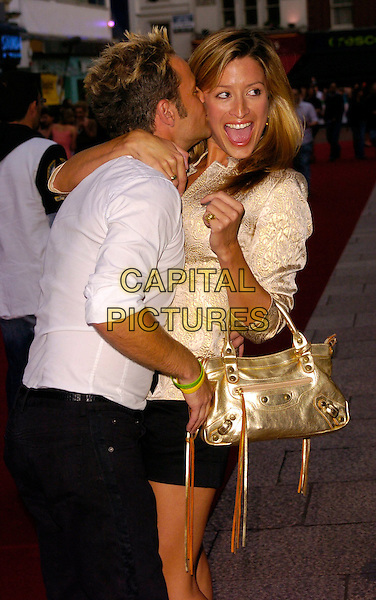 """JULIAN BENNETT & REBECCA LOOS.""""You, Me & Dupree"""" UK film premiere, Odeon, Leicester Square, London, UK..August 22nd, 2006.Ref: CAN.half length black shorts gold purse bag jacket cream hug embrace mouth open kiss gesture.www.capitalpictures.com.sales@capitalpictures.com.©Can Nguyen/Capital Pictures"""