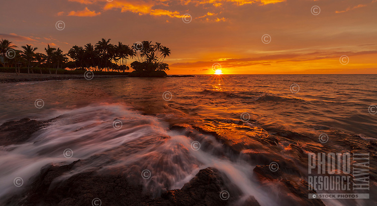 A colorful sunset silhouettes palm trees and the rocky shoreline at Pauoa Bay on the Big Island of Hawai'i.