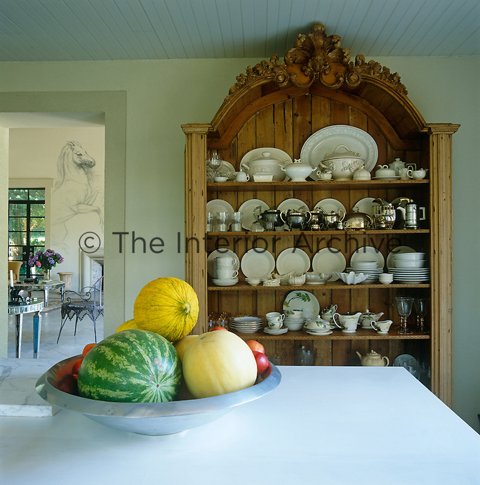 In the kitchen an antique English pine cabinet displays a 19th-century tea service, Irish antique creamware and Wedgwood shell plates