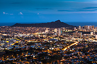An aerial view at night of Manoa and other Honolulu neighborhoods with Diamond Head in the distance, as seen from Tantalus Lookout at Pu'u 'Ualaka State Park, O'ahu.