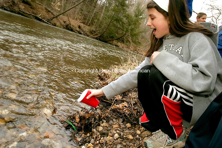 SOUTHBURY, CT--05 APRIL 2007--040507JS02- Julia Cipriano, a seventh grader from Memorial Middle School in Middlebury, releases one of 98 brook trout into the Pomperaug River at the Bent of the River Audubon Center in Southbury. The seventh graders, from the middle school's Life Science class, raised the trout as part of Trout in the Classroom educational program with the Naugatuck Pomperaug Chapter of Trout Unlimited. <br /> Jim Shannon / Republican-American