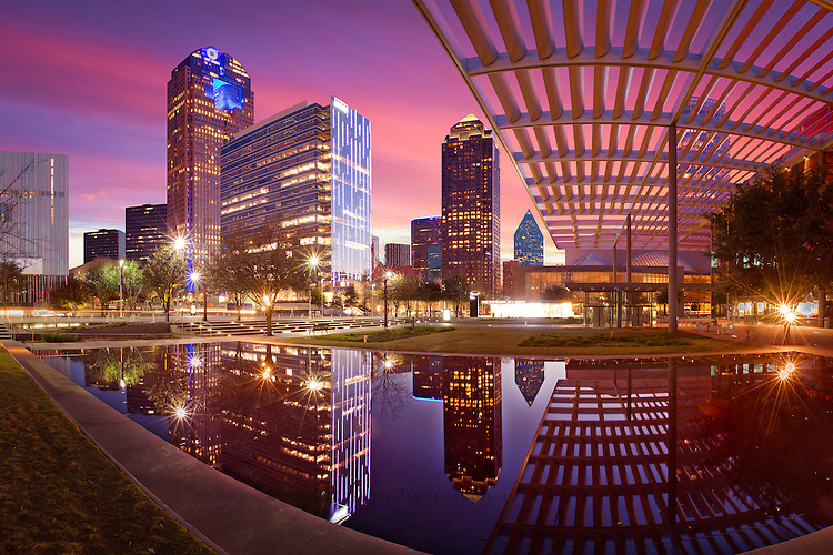 """Dallas Arts District at Sunset with Reflection"" - Glowing in the late afternoon light, sunset envelopes the radiant Dallas Arts District in incandescent tones of saffron, lavender, wisteria, and marigold. In the foreground, the Arts District and Winspear Opera House are reflected in the Donor Reflecting Pool at Sammons Park."