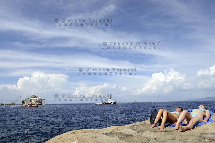 Isola del Giglio, 21 Luglio 2014<br /> Operazione di rimozione della nave da crociera Costa Concordia, naufragata il 13 Gennaio del 2012.<br /> Turiste al sole su uno scoglio.<br />  Concordia Wreck Removal Project, Giglio Island