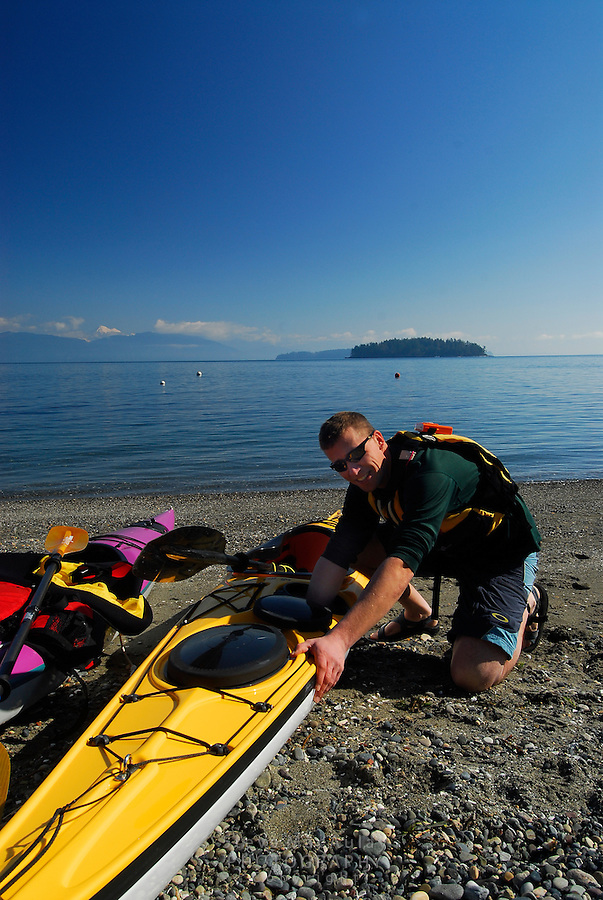 Male paddler preparing purple and yellow kayaks for a day of paddling in the San Juan Islands, Sea Kayaking the San Juan Islands, WA.