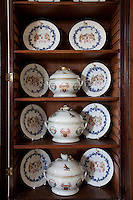 A collection of antique china baring the Munro coat of arms in the drawing room cabinet