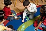 Education Preschool 3-5 year olds female teacher sitting on floor with group of children number activity putting circles with numbers on them in order horizontal