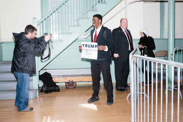 """Vincent Vaughns, 18, a high school senior at Phillips Exeter Academy, holds a campaign sign autographed by the candidate after real estate mogul and Republican presidential candidate Donald Trump spoke at a rally at Exeter Town Hall in Exeter, New Hampshire, on Thurs., Feb. 4, 2016. Vaughns said he is leaning towards Trump in the election. """"I wanted to hear straight from his face what he's going to do for America,"""" he said."""