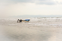 Fisherman launches his boat in to the surf at Dawn. Canoa, Ecuador