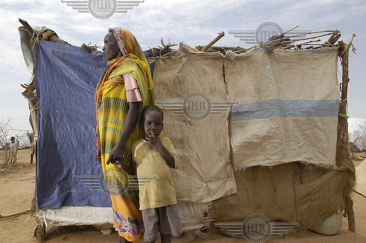 Woman and child in the Bilel camp for internally displaced persons (IDPs). A distribution of plastic sheeting was made by the UNHCR to strengthen shelters as the rainy season began. The residents of the camp fled their homes after being attacked by Janjaweed militias.