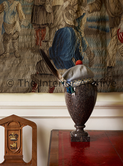 A Scottish bonnet graces a porphyry urn on the hall table