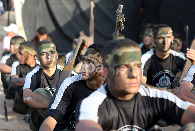 Palestinian youths take part in a graduation ceremony of a military-style summer camp organized by the Hamas movement in Gaza City June 19, 2014. Hamas stages dozens of military-style summer camps for young Palestinians in the Gaza strip to prepare them to confront any possible Israeli attack, organisers said. Photo by Ezz Zanoun