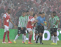 BOGOTÁ -COLOMBIA, 07-05-2014. Jugadores de Santa Fe y Nacional discuten con el árbitro, Luis Sanchez (de azul) tras suspender por lluvia el encuentro de ida entre Independiente Santa Fe y Atlético Nacional por la semifinales de la Liga Postobón I 2014 jugado en el estadio Nemesio Camacho El Campín de la ciudad de Bogotá./ Players of Santa Fe and Nacional  discussed with Luis Sanchez, referee, after he suspended due to rain the first leg match between Independiente Santa Fe and Atletico Nacional for the semifinals of the Postobon League I 2014 played at Nemesio Camacho El Campin stadium in Bogotá city. Photo: VizzorImage/ Gabriel Aponte / Staff