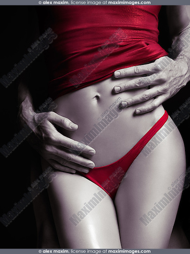 Man hands embracing young sexy woman in red underwear. Sensual couple artistically processed black and white photo.