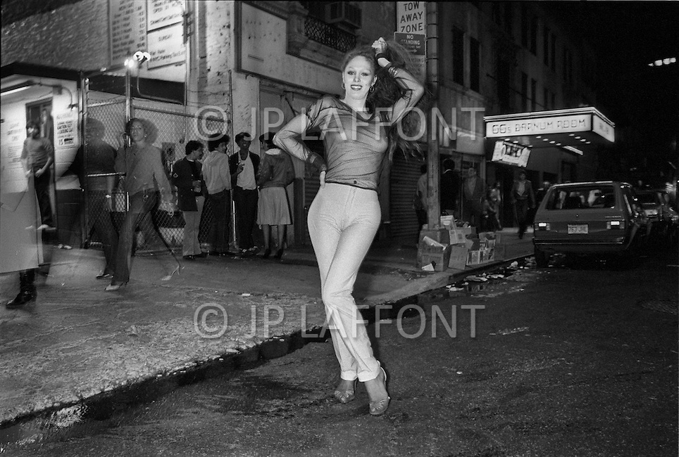 May, 1980. Manhattan, New York City, NY. A prostitute leans playfully on a cop car on 42nd Street Times Square. The police struggled to keep up with onslaught of crime in the area and at times seemed to be playing a friendly game of cat and mouse with the hookers. <br />