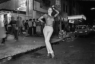May, 1980. Manhattan, New York City, NY. A prostitute leans playfully on a cop car on 42nd Street Times Square. The police struggled to keep up with onslaught of crime in the area and at times seemed to be playing a friendly game of cat and mouse with the hookers. <br /> <br /> Manhattan, New York City, NY, Mai, 1980. 1 heure du matin: Cette prostitu&eacute;e nargue les policiers en prenant des poses aguichantes contre leur voiture. Les policiers sont bons enfants et acceptent en riant ces situations extr&ecirc;mes.
