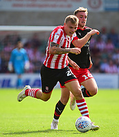 Lincoln City's Harry Anderson vies for possession with Swindon Town's Martin Smith<br /> <br /> Photographer Andrew Vaughan/CameraSport<br /> <br /> The EFL Sky Bet League Two - Lincoln City v Swindon Town - Saturday August 11th 2018 - Sincil Bank - Lincoln<br /> <br /> World Copyright &copy; 2018 CameraSport. All rights reserved. 43 Linden Ave. Countesthorpe. Leicester. England. LE8 5PG - Tel: +44 (0) 116 277 4147 - admin@camerasport.com - www.camerasport.com