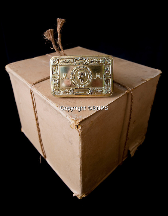 BNPS.co.uk.(01202 558833)<br /> Pic: PhilYeomans/BNPS<br /> <br /> The unopened box with a tin given to auctioneer Patrick Bogue's own father.<br /> <br /> 100 year old time capsule from Xmas 1914 discovered.<br /> <br /> A time capsule box of Christmas gifts originally destined for First World War troops fighting in the trenches in 1914 is to be opened for the first time after it emerged for sale.<br /> <br /> X-rays have shown that the unremarkable brown cardboard box contains 81 brass tins containing gifts for front line soldiers sent from the Royal family.<br /> <br /> The brass tins held cigarettes, pencils made from shell casings, chocolate, sweets and even Christmas cards.<br /> <br /> They were made in their thousands then shipped off to soldiers fighting in the trenches over the first Christmas of the Great War.<br /> <br /> But one box never made it to its intended destination and is now up for sale 100 years on for almost &pound;30,000 after being discovered by a collector.<br /> <br /> It will be opened for the first time by Lady Emma Kitchener, great-grandniece of military leader Herbert Kitchener, at the Chalke Valley History Festival near Salisbury, Wilts.<br /> <br /> A select amount of tins will be sold at the festival for &pound;300 with the rest being auctioned at Onslows in Blandford, Dorset, on July 9.