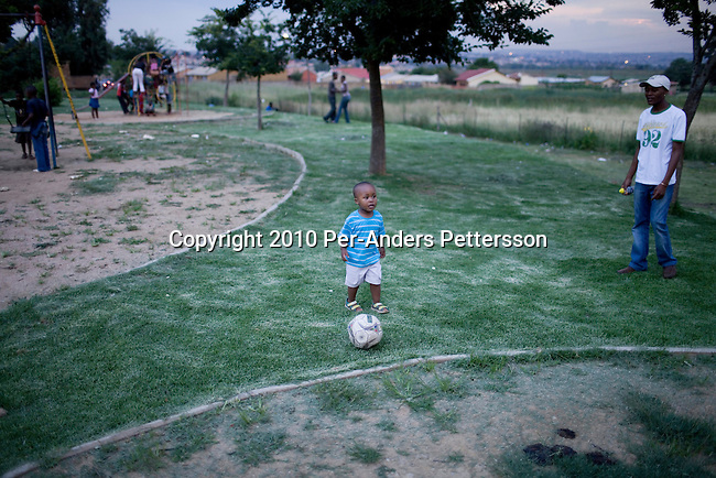 SOWETO, SOUTH AFRICA - JANUARY 15: Thami Nkosi, a 29-year old activist, plays soccer with his son Tumi on January 15, 2010, in Soweto, South Africa. Thami is a gender justice activist and often counsels men how to use condoms and not to cheat or abuse women. He is part of the new young generation of black South African's who has got better education opportunities. Soweto is the largest township in South Africa, located about 10 kilometers southwest of downtown Johannesburg. The population is estimated to be around 2-3 million. (Photo by Per-Anders Pettersson/Getty Images)