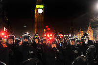 Police stand guard on Parliament Square outside the Houses of Parliament during a student demonstration in Westminster, central London on the day the government passed a bill to increase university tuition fees.