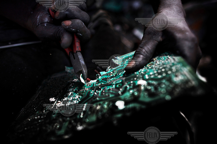 A man rips apart a circuit board to salvage components, at Agbogbloshie dump, which has become a dumping ground for computers and electronic waste from all over the developed world. Hundreds of tons of e-waste end up here every month. It is broken apart, and those components that can be sold on, are salvaged.