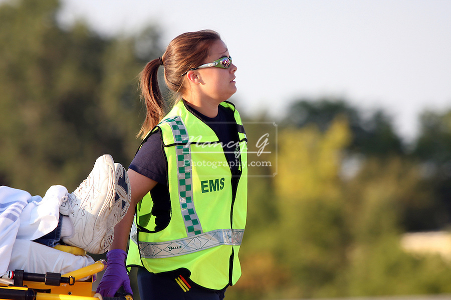 A female EMS personnel bringing an injured person on a cot to an ambulance at a mass casualty scene in Waukesha Wisconsin