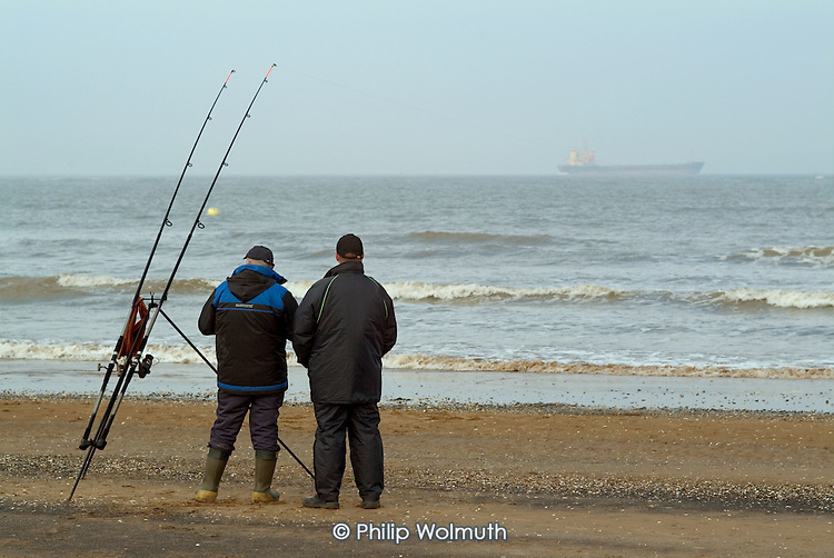 Men fishing on the beach at the seaside holiday resort of Cleethorpes, on the outskirts of the declining fishing port of Grimsby.