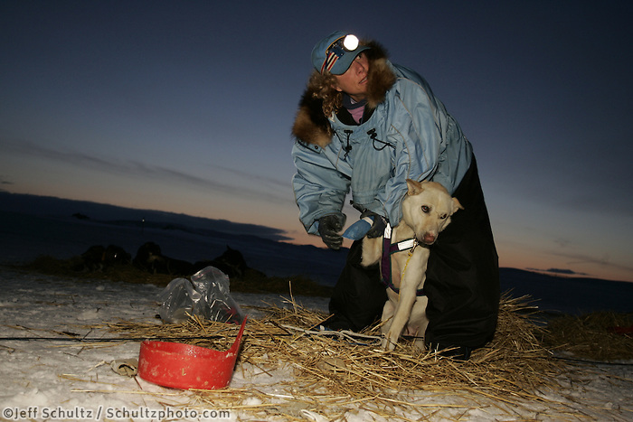 Dee Dee Jonrowe boots her dogs as the sun begins to rise on Monday morning at Unalakleet,  2005 Iditarod Trail Sled Dog Race.