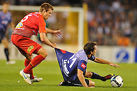 MELBOURNE, AUSTRALIA - JANUARY 23, 2010: Robbie Kruse from Melbourne Victory is fouled by Daniel Mullen from Adelaide United in round 24 of the A-league match between Melbourne Victory and Adelaide United FC at Etihad Stadium on January 23, 2010 in Melbourne, Australia. Photo Sydney Low www.syd-low.com