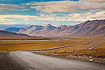 Pipeline along Dalton Hwy in a fall colored tundra valley. The mountains in Arctic National Wildlife Refuge are in the background. Arctic Alaska, Autumn.