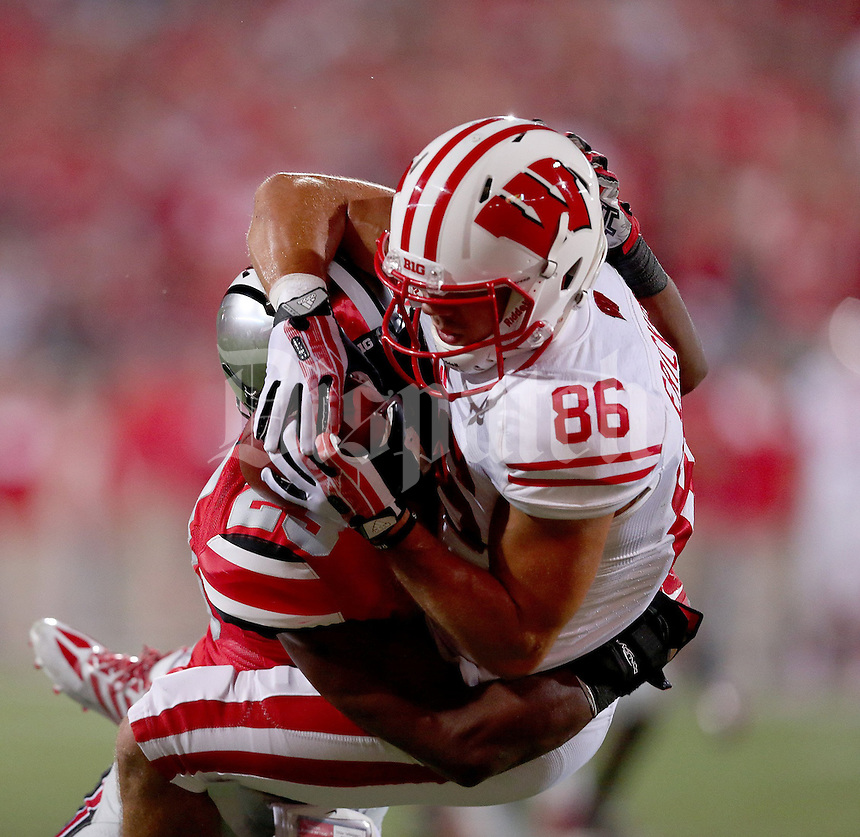 Ohio State Buckeyes defensive back Tyvis Powell (23) slams Wisconsin Badgers wide receiver Alex Erickson (86) to the ground causing an incompletion in the end zone during the fourth quarter of the game between Ohio State and Wisconsin at Ohio Stadium on Saturday, September 28, 2013. (Columbus Dispatch photo by Jonathan Quilter)