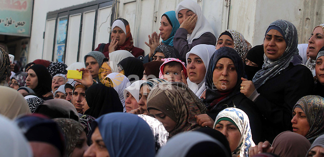 Palestinian women watch during the funeral of three Palestinians: Yazan Basim, Mahmoud Abu Zena and Hamza Abu Al-Haija, at Jenin Refugee Camp in Jenin, West Bank, 22 March 2014. Three Palestinians were killed and at least nine wounded during clashes with Israeli forces. One of those killed was Hamza Abu al-Haija, a militant leader in Hamas (Al Qasam Brigade). Abu al-Haija, 23, the son of a senior Hamas leader currently serving nine life terms in Israeli jails, refused to surrender and the army opened fire at the house, killing him. Photo by Issam Rimawi