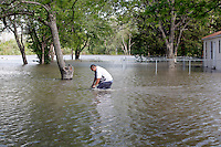 Gabriel Yanes peddles his bike through floodwaters near the intersection of North Main Street and Second Street in the Red Star District of Cape Girardeau, MO, on Thursday, April 28, 2011.