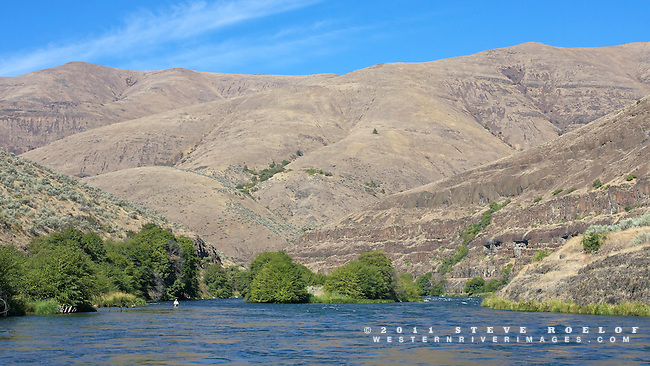 A fly fisherman wades in the Deschutes River.
